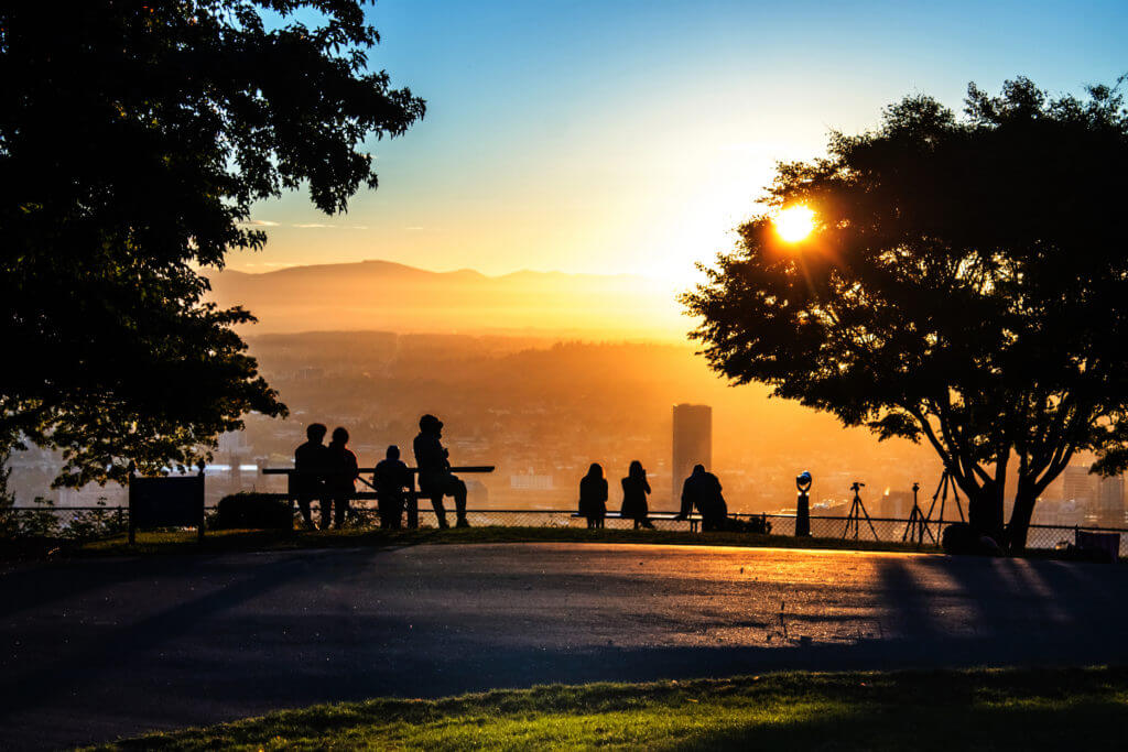 "Early morning sightseers and photographers gather together on the overlook at Pittock Mansion west of Portland, Oregon. The building dubbed ""Big Pink"" stands tall as the first rays of daylight warm the waking city."